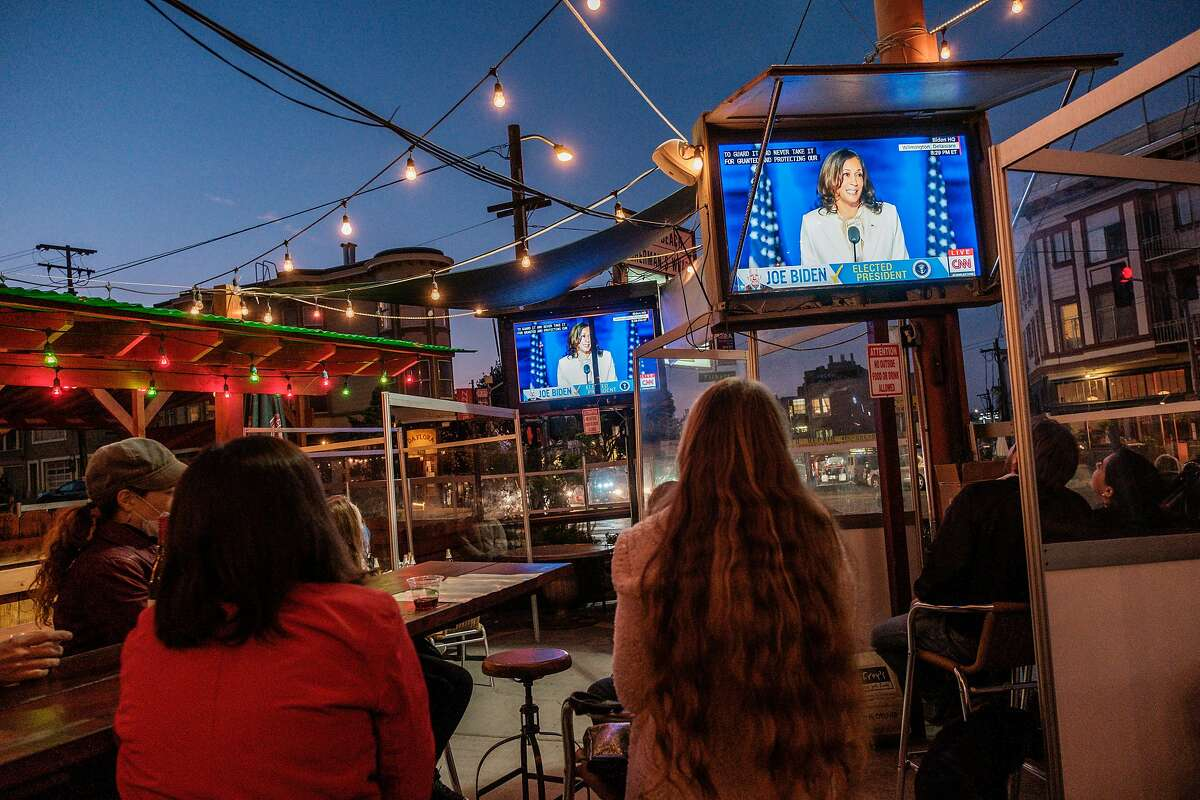 People watch Vice President Elect Kamala Harris speak on television at Piazza Pellegrini in North Beach in San Francisco on Saturday, November 7, 2020.