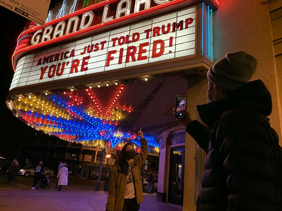 """Adrienne Lam has her photo taken by Andrew Lee, both of Oakland, underneath the marquee at Grand Lake Theater that reads, """"America just told Trump, 'You're Fired,'"""" on Saturday, November 7, 2020, in Oakland, Calif. """"I've been crying all day. Just tears of happiness, relief and joy,"""" Lam said. """"It's the first time we've heard a leader in a long time."""" (Yalonda M. James / The Chronicle)"""