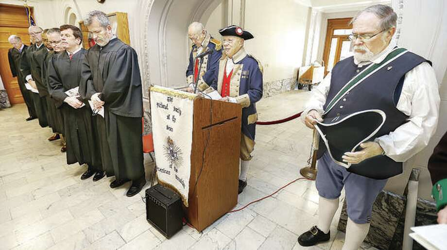 In this Nov. 7, 2019 file photo, Chaplain Lloyd Schwarz, center, delivers the invocation with eight Madison County judges in attendance, left, during the 23rd Annual Flag Award Ceremony held in the lobby of the Madison County Courthouse in Edwardsville by members of the Gen. George Rogers Clark Chapter, Illinois Society of Sons of the American Revolution. In all, twelve households were honored for their flying of the American flag and received an award from the SAR. Photo: John Badman | Hearst Newspapers