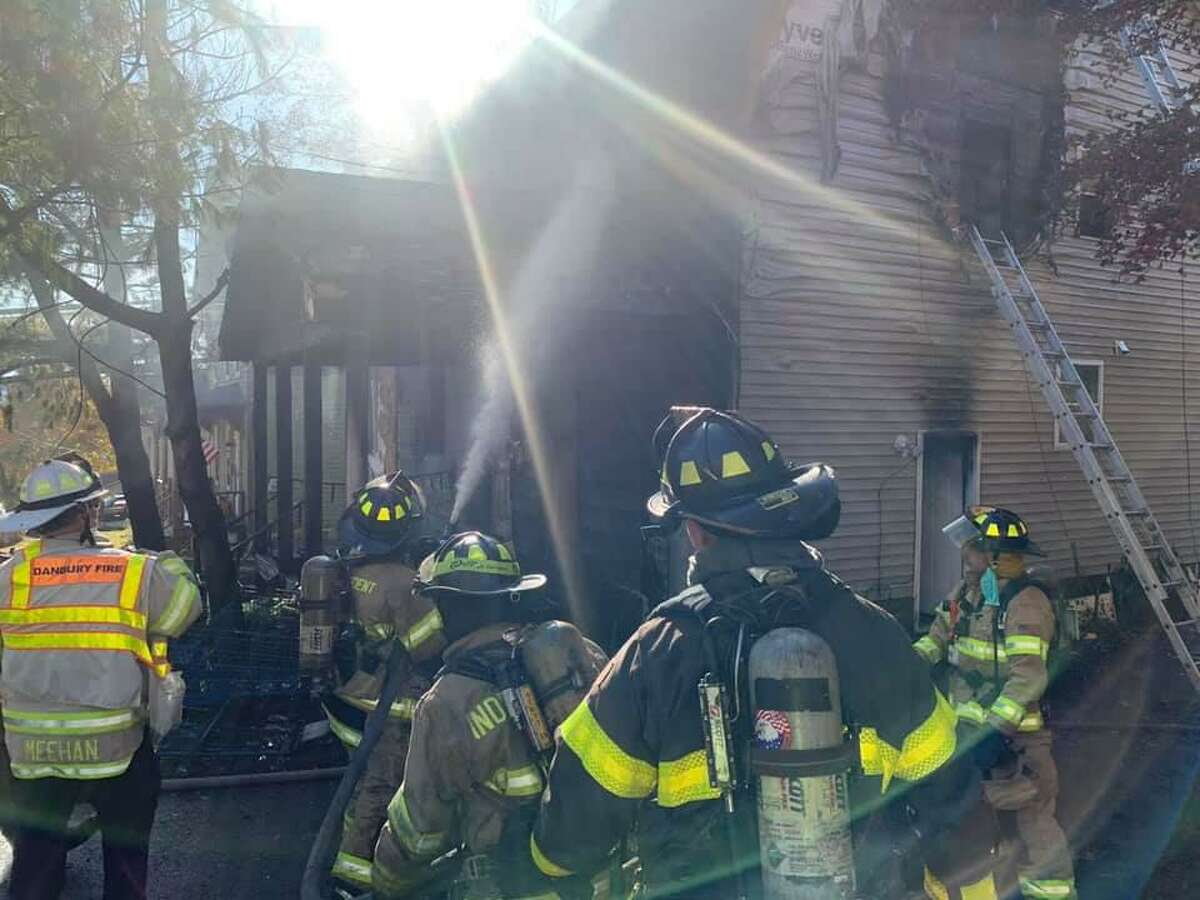 Danbury firefighters at the scene of Saturday's fire on Rowan Street, which left two people hurt and 16 without a place to stay.