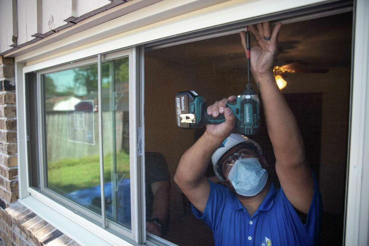 Harry Buler, master craftsman at Power Home Remodeling, drills in the frame during a window installation in Spring, Texas on Oct. 6, 2020.