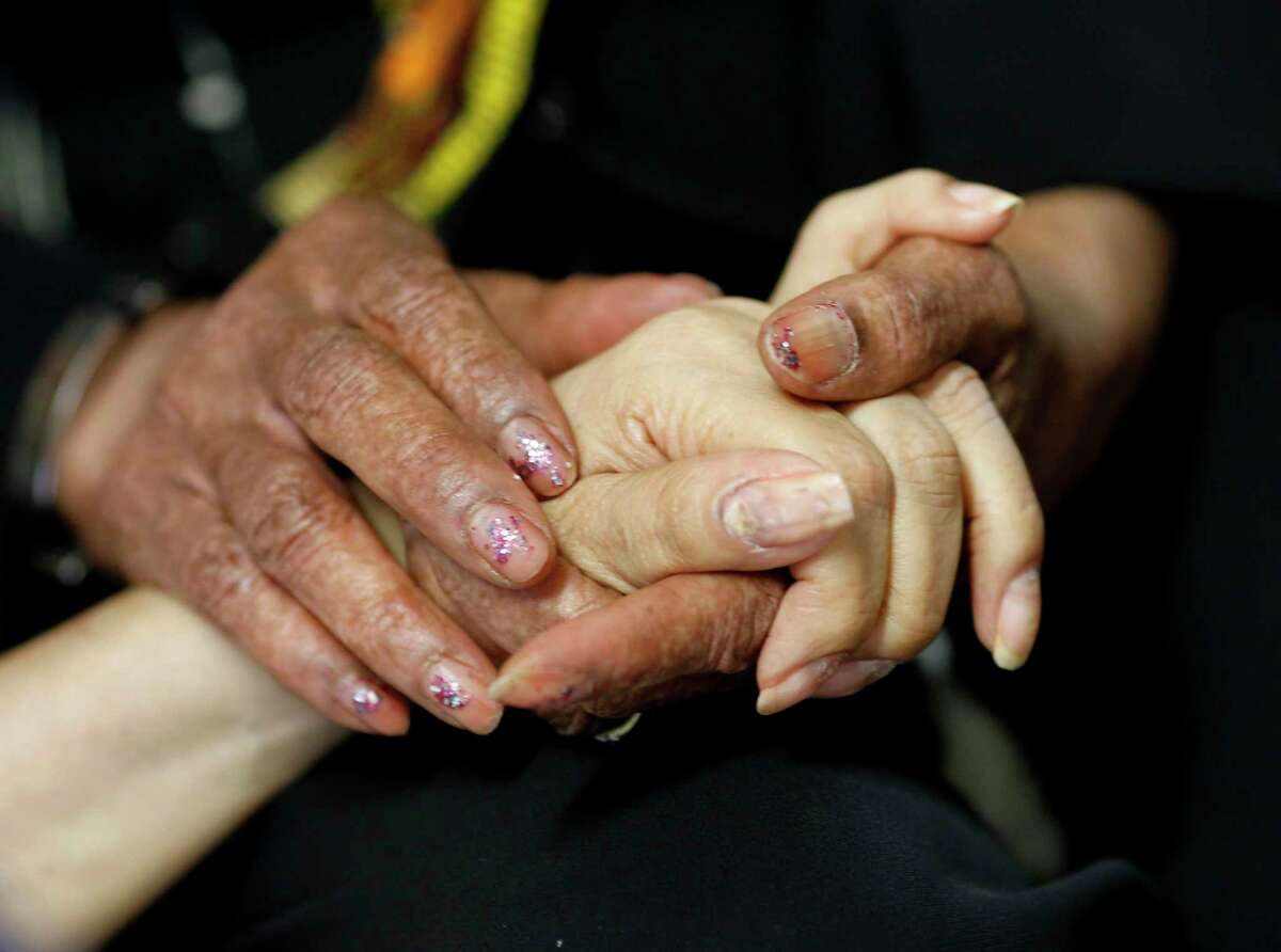 A patient has her hand held by a chaplain during a hospital room visit in 2013. Palliative care specializes in the relief of pain, symptoms and stress of serious illness, and is becoming more common in hospitals.