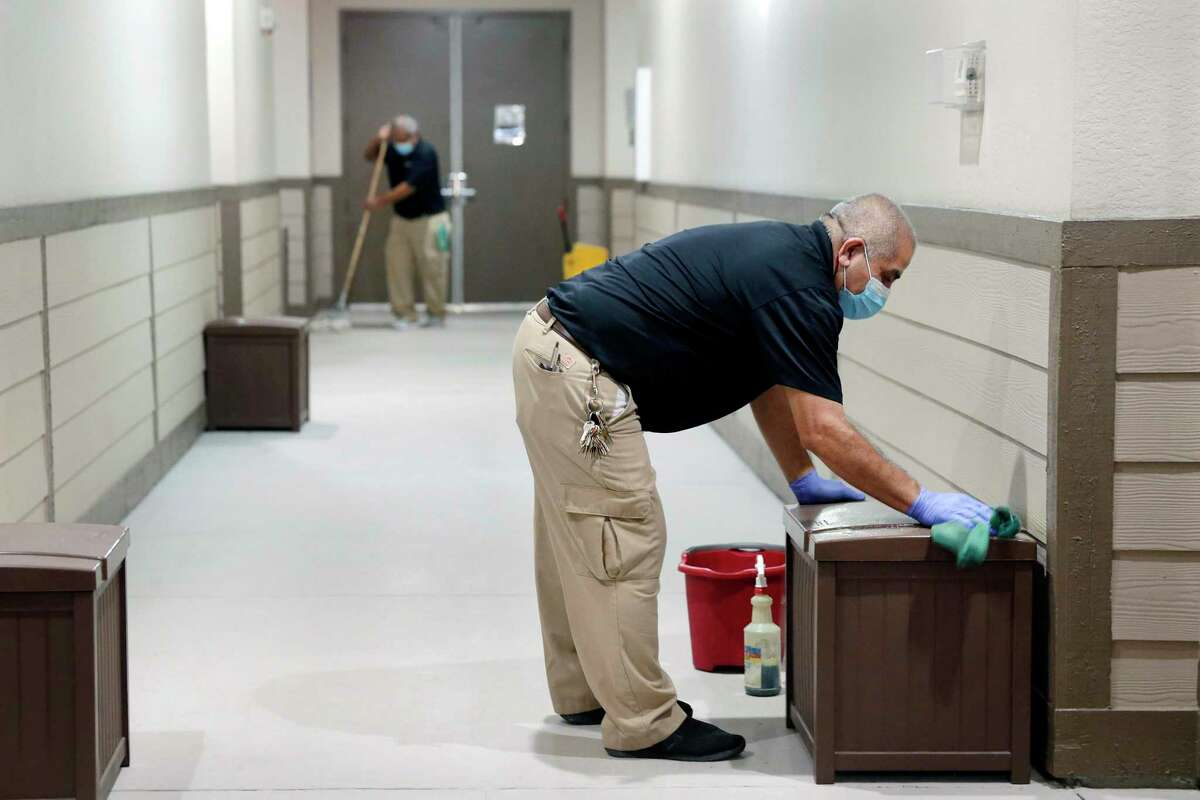 Maintenance employee Lazaro Gomez, right, wipes down trash receptacles as Juan Robles, left, mops in the hallways outside of individual apartments at the Camden Plaza apartment complex Tuesday, Oct. 13, 2020 in Houston, TX.