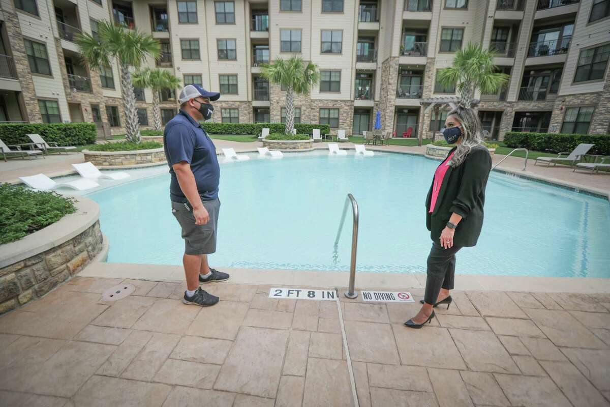 Hilltop Residential's on-site employees have been working at the properties throughout the pandemic. Assistant Service Techician Norberto Figueroa talks to Community Director Monica Bonilla poolside at Waterside Village in Richmond.