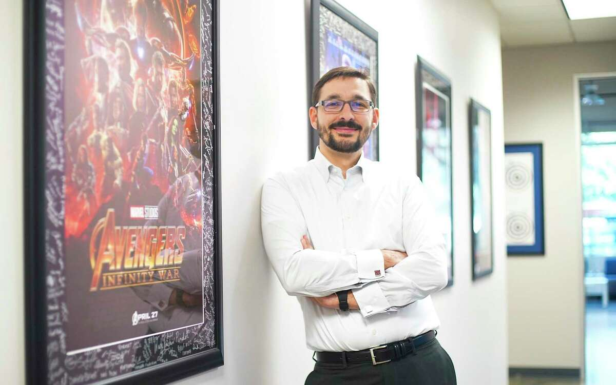 Devlin Liles, president of Improving Houston, stands by a row of movie posters in the hallway. The business was named No.1 among small companies in the 2020 Top Workplaces.