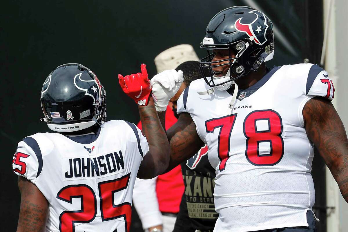 Houston Texans running back Duke Johnson (25) and offensive tackle Laremy Tunsil (78) do a fist bump before an NFL football game at TIAA Bank Field Sunday, Nov. 8, 2020, in Jacksonville.