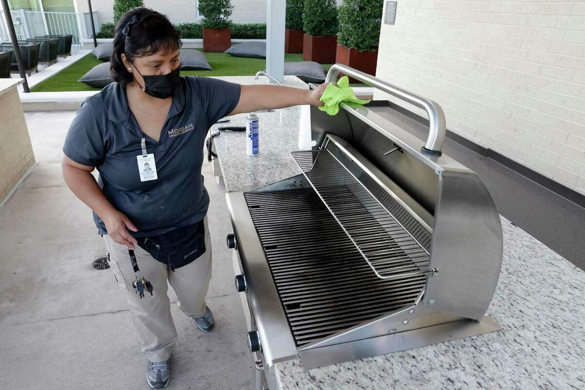 Lilia Medina, with house keeping, cleans a grill on an outdoor patio deck at the Pearl Marketplace at Midtown apartment complex Thursday, Oct. 15, 2020, part of the Morgan Group in Houston, TX.