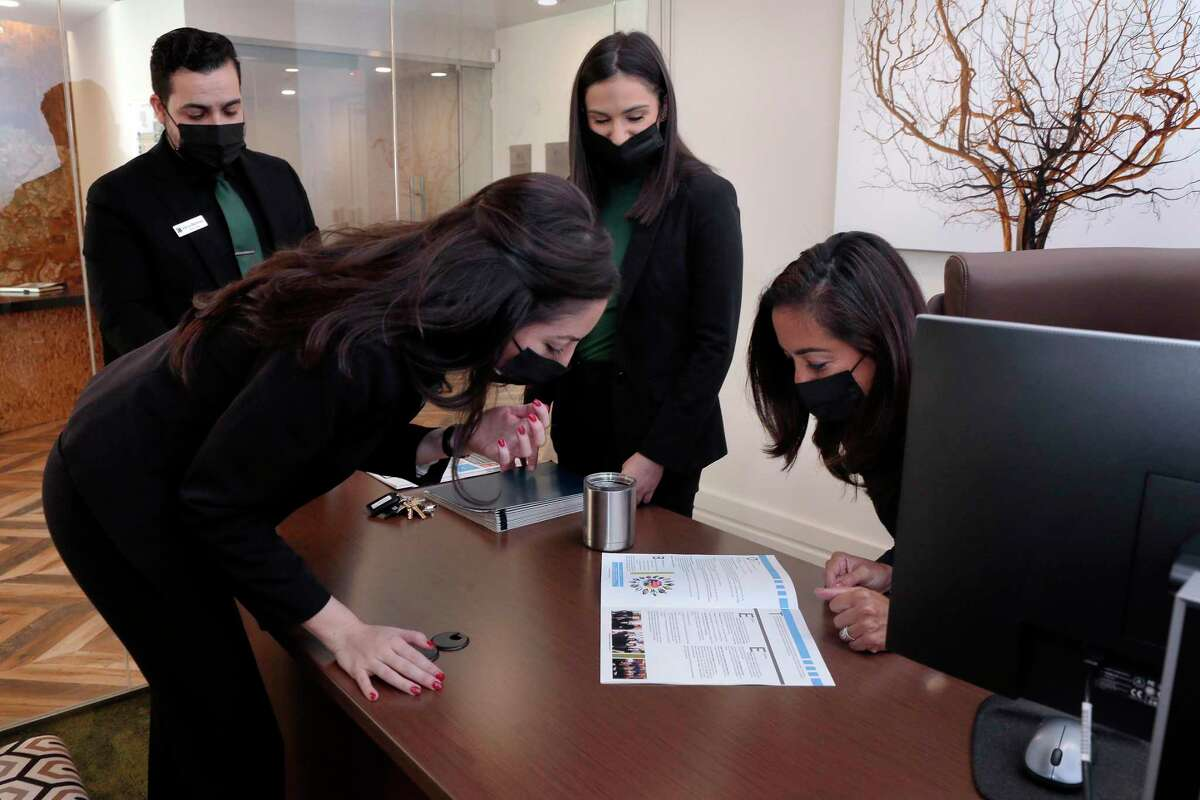 From left, Adrian Martinez, Angela Gomez, Lauren DeJoe and LuzDonovan look over a recent promotional brochure in Gomez's office at the Pearl Marketplace at Midtown apartment complex Thursday, Oct. 15, 2020, part of the Morgan Group in Houston, TX.