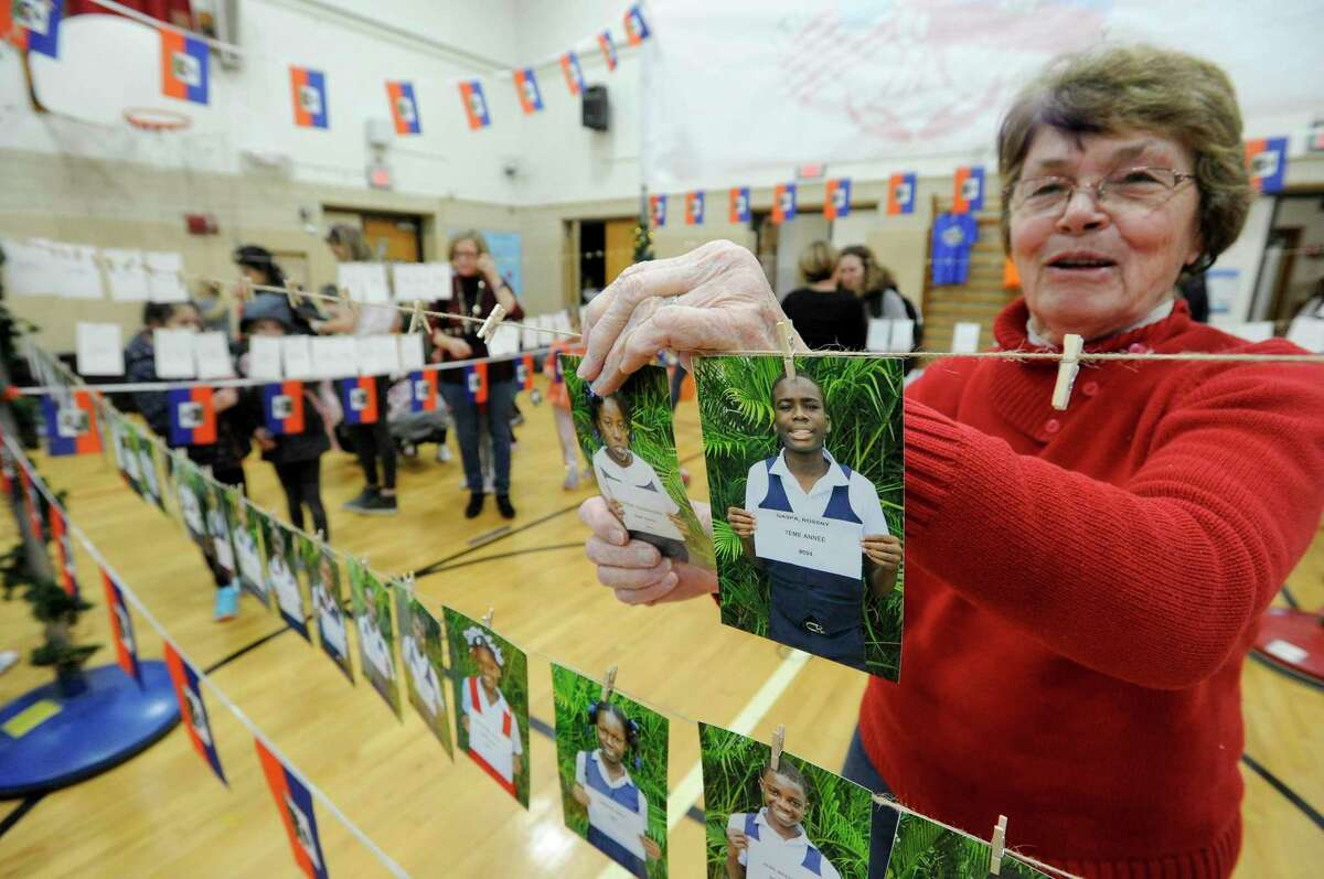 """Carole Younkman, a volunteer and grandparent of a student at Riverside School in Greenwich, Conn., arranges photos of Haitian children, as the school kick's off the second annual school-wide community service event, """"Holidays for Haiti."""" last year. The event is virtual this year."""