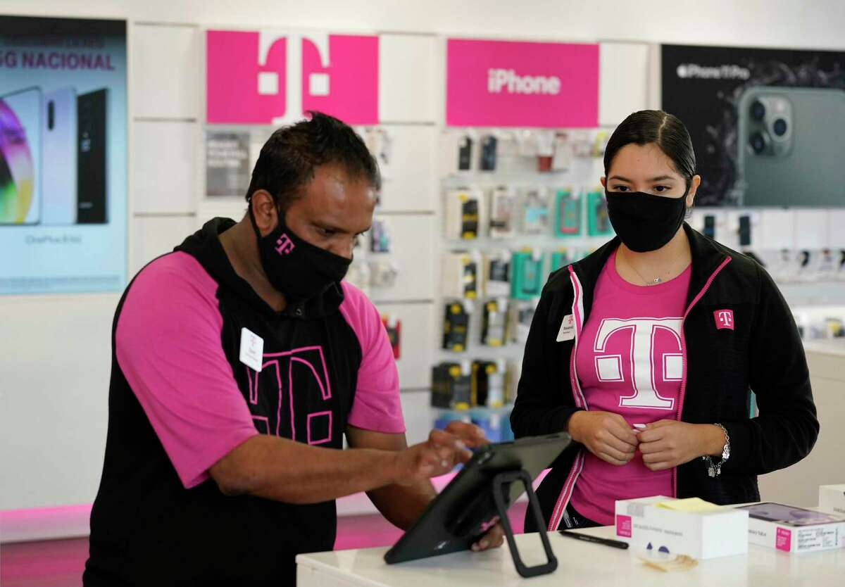 Syed Ahmed, manager, left, and Yessenia Carmona, mobile expert, right, work at T Mobile, 4400 North Fwy., Monday, Aug. 12, 2020 in Houston.