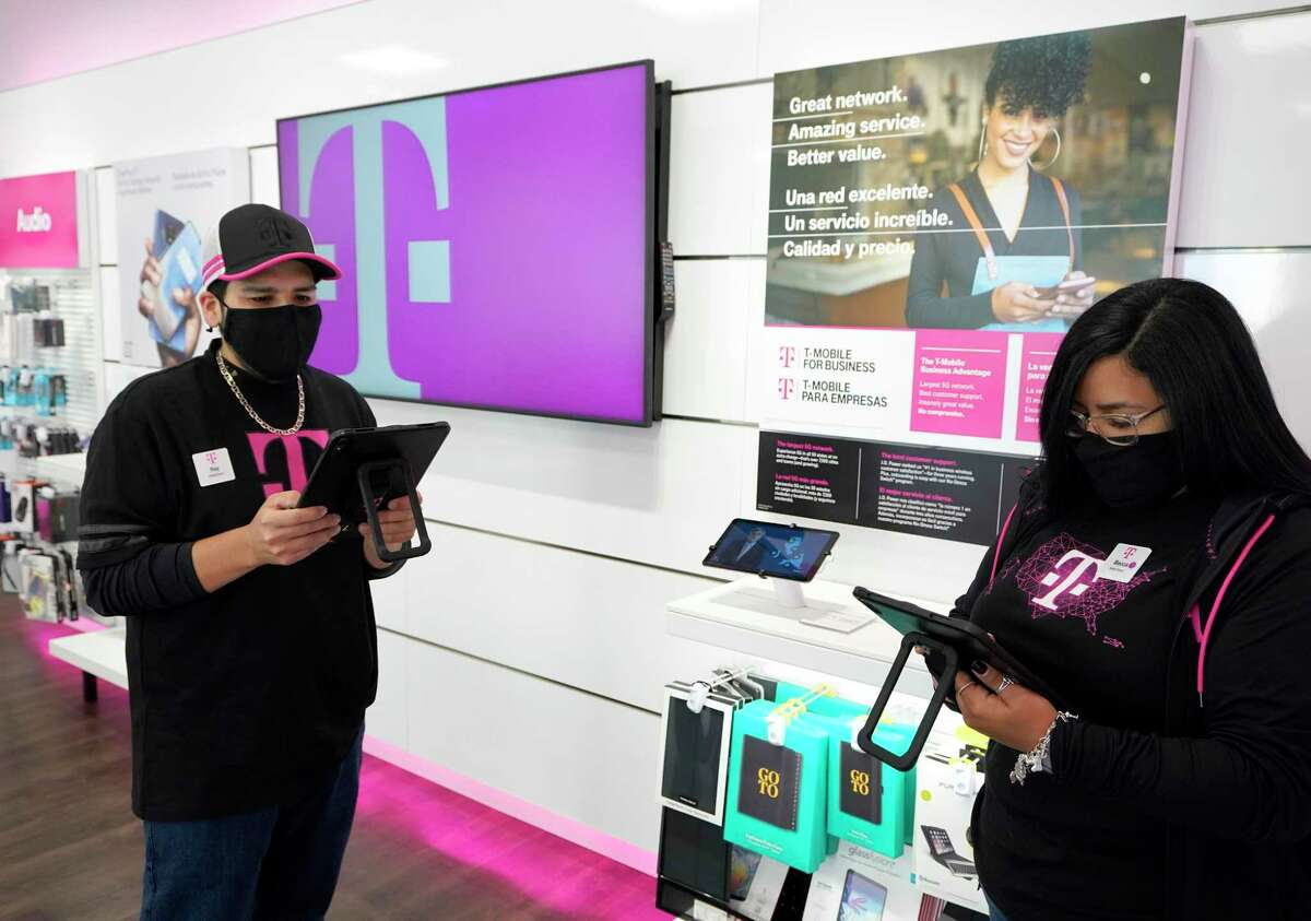 Mobile experts, Ray Orozco, left, and Rebecca Martinez, right, work at T Mobile, 4400 North Fwy., Monday, Aug. 12, 2020 in Houston.