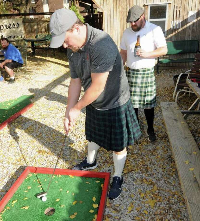 Seth Bohnenstiehl of Highland and his kilt-wearing team finish the Corner Keg Pub course Saturday during the Highland Jaycees Putt Putt Bar Crawl fundraiser.