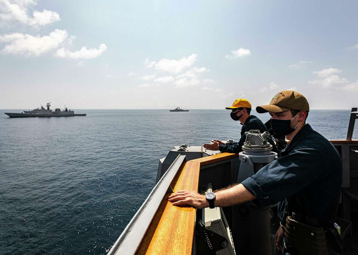 Lt. j.g. Daniel Feeney, left, a U.S. Navy navigator from Old Greenwich, stands watch on the bridge wing aboard the guided-missile destroyer USS John S. McCain as the ship sails in the Indian Ocean in formation with ships and a submarine during a photo exercise as part of Malabar 2020.