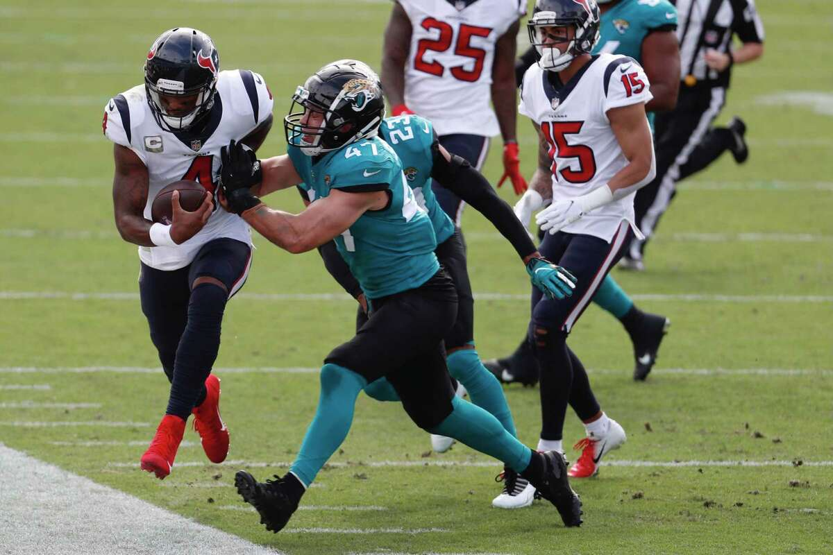 Houston Texans quarterback Deshaun Watson is knocked out of bounds as he scrambles out of the pocket against the Jacksonville Jaguars during the first half an NFL football game at TIAA Bank Field Sunday, Nov. 8, 2020, in Jacksonville, Fla.