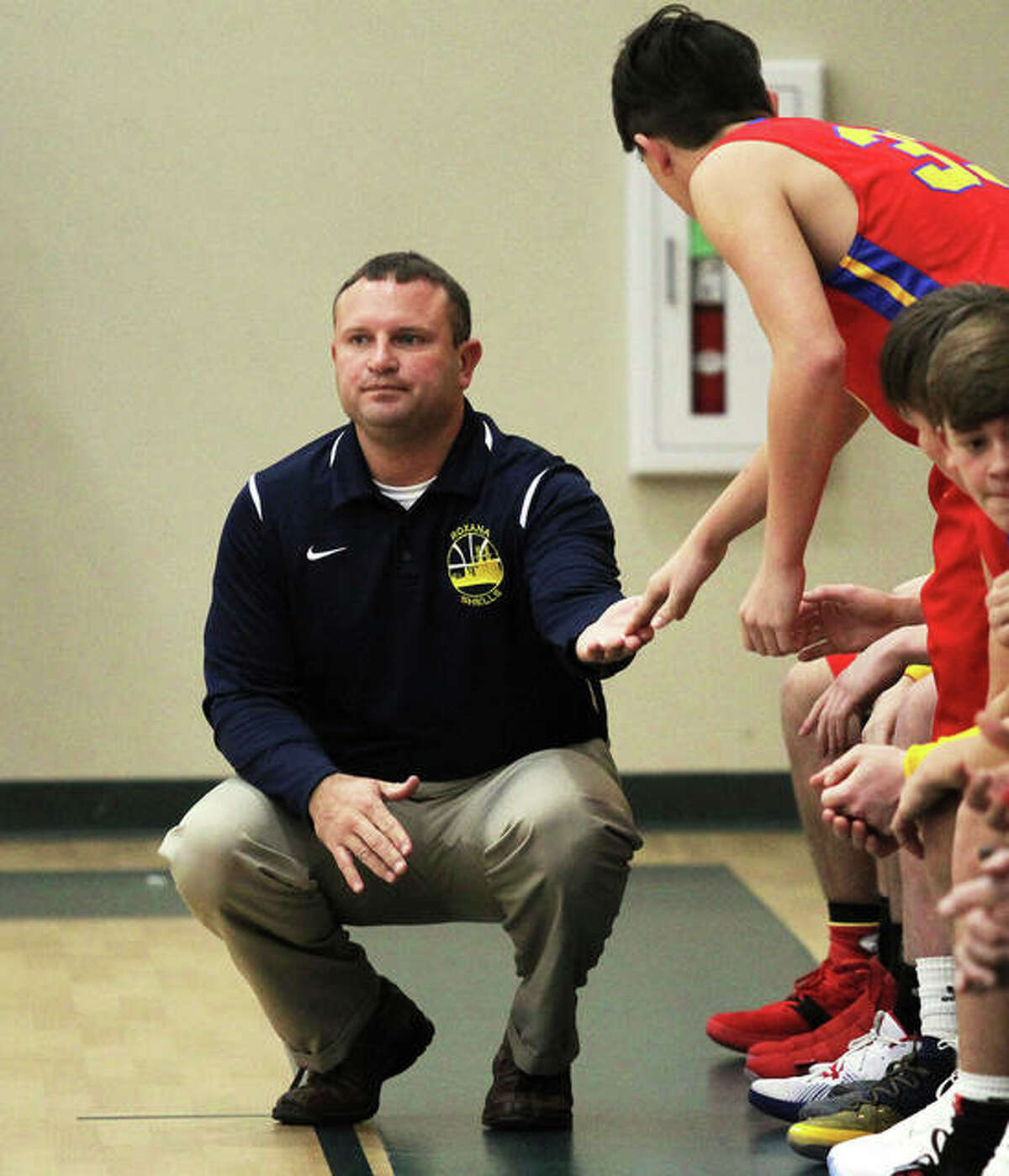 Roxana coach Mark Briggs welcomes a Shell back to the bench during a 2018 game at the Metro-East Lutheran Thanksgiving Tournament in MEL's aux gym in Edwardsville.