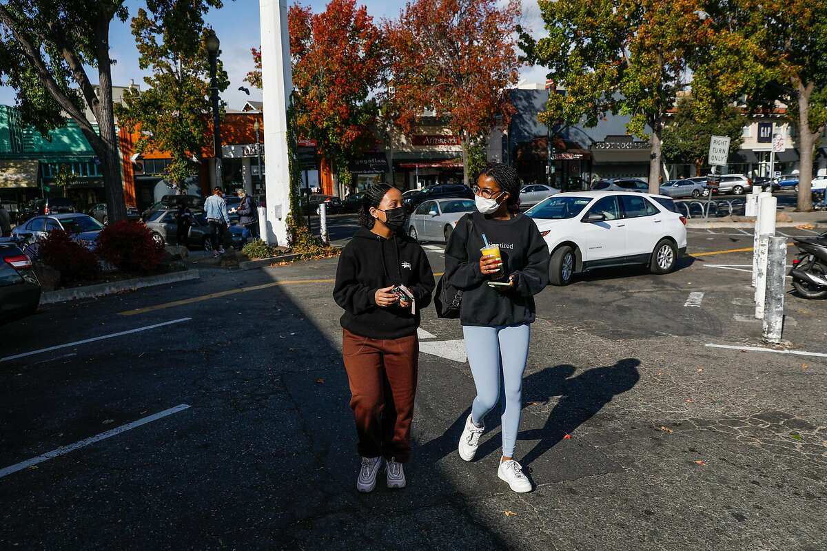 (L-r) Haime Belay, 18 and Amaya Weekes, 17 walk back through the parking lot off of Lakeshore Avenue after speaking to the Chronicle about the Presidential election on Sunday, Nov. 8, 2020 in Oakland, California.