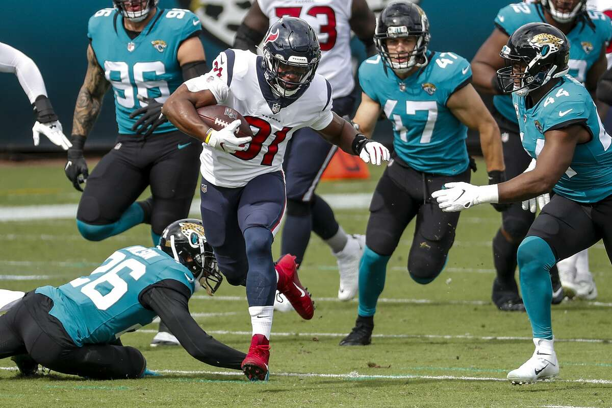Houston Texans running back David Johnson (31) runs past Jacksonville Jaguars free safety Jarrod Wilson (26) during the first half of an NFL football game at TIAA Bank Field Sunday, Nov. 8, 2020, in Jacksonville.