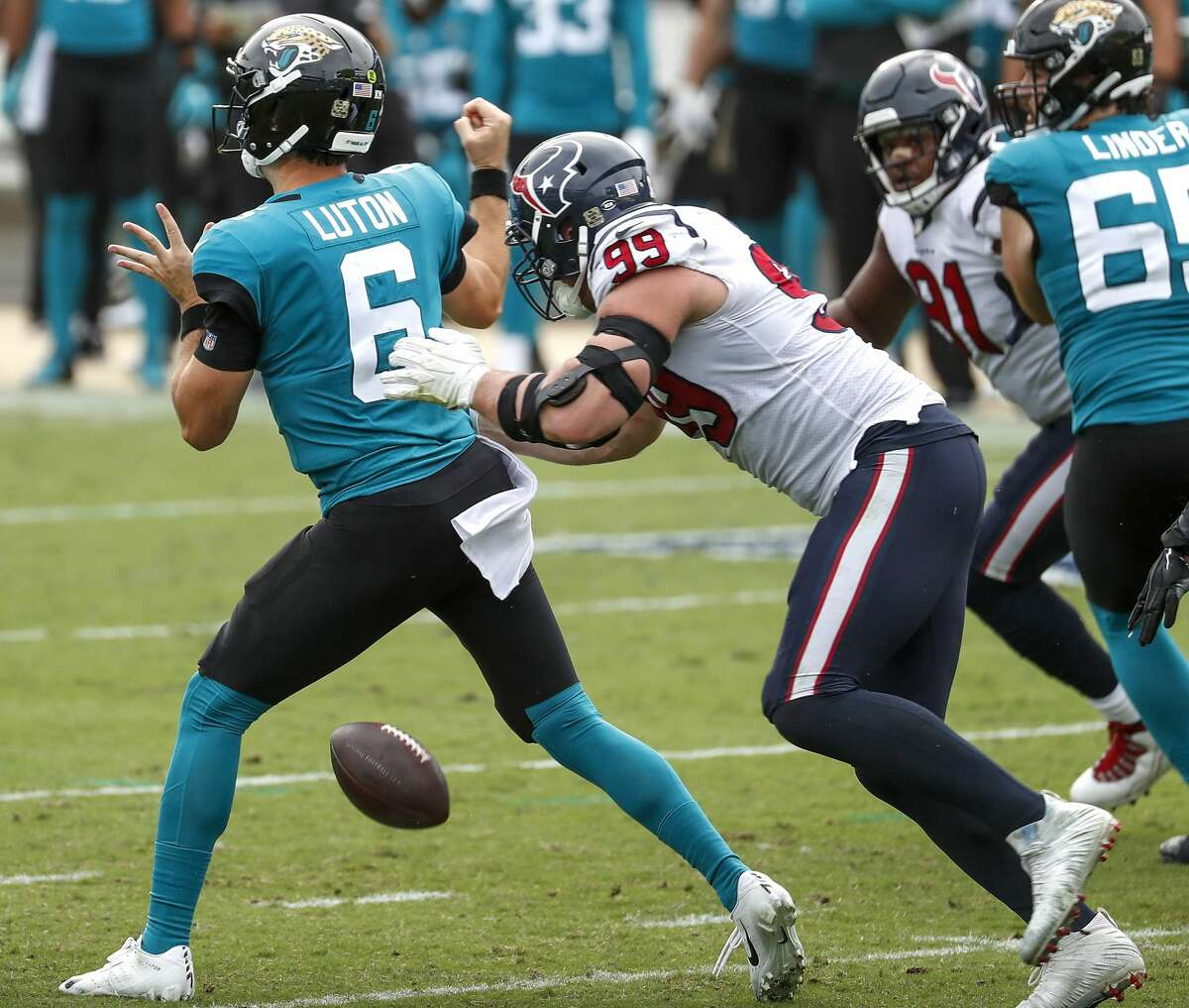 Houston Texans defensive end J.J. Watt (99) strips the ball away from Jacksonville Jaguars quarterback Jake Luton (6) as he sacks the quarterback during the second half of an NFL football game at TIAA Bank Field Sunday, Nov. 8, 2020, in Jacksonville. The sack was Watt's 100th career sack.