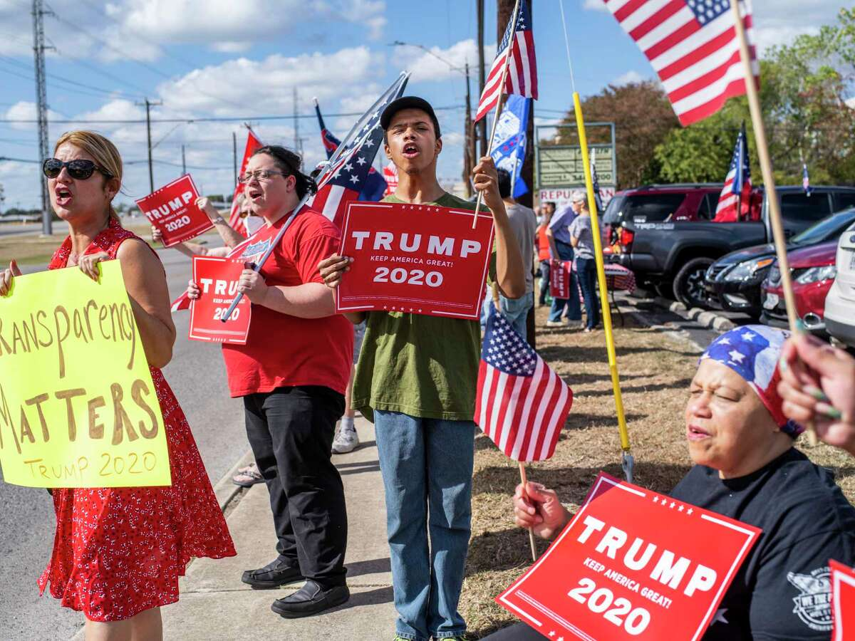 Supporters of President Trump hold a flag-waving rally put on by the group Log Cabin Republicans outside of Republican headquarters in San Antonio on Sunday, Nov. 8, 2020. Many at the rally said they don't believe Trump lost.