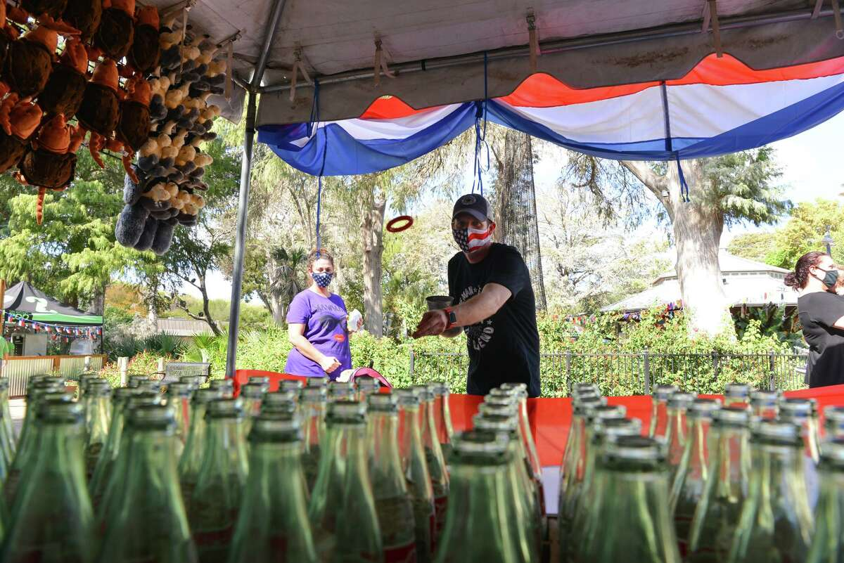 Michael Baudoin plays the ring toss game as his wife Tonya looks on during the On a Stick! Festivals You Missed Sunday at the San Antonio Zoo.