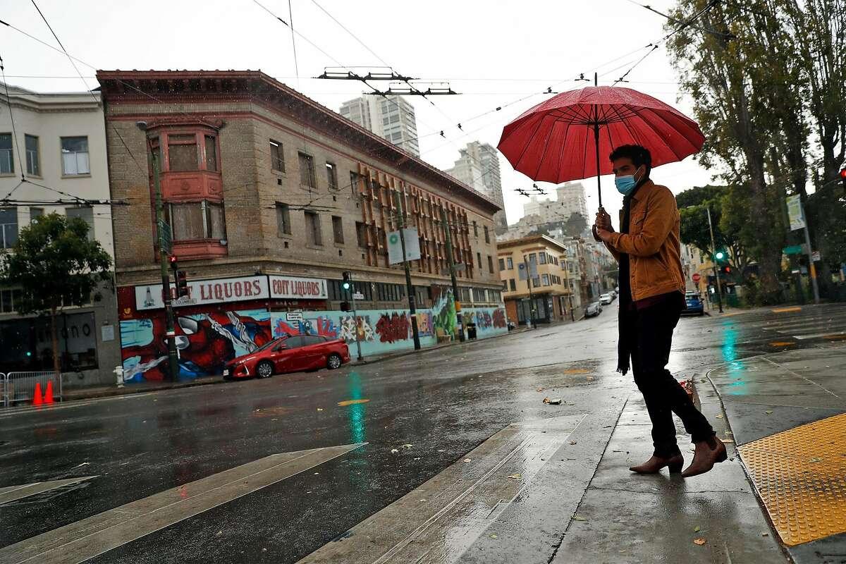 Ali Moosa crosses Union Street in San Francisco as a shower passes.