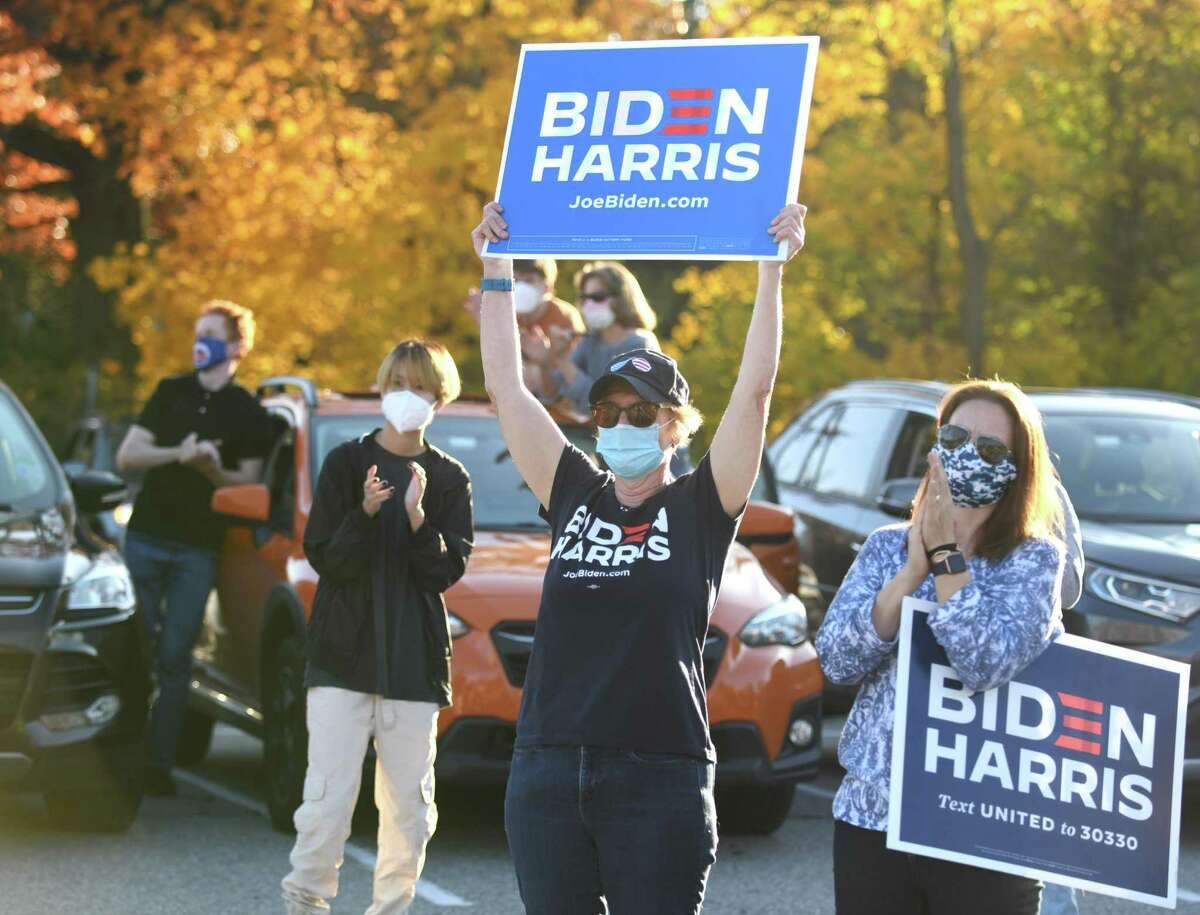 Darien's Ann Reed, center, and Sarah Neumann, right, hold signs and celebrate during the Joe Biden and Kamala Harris rally at the Noroton Heights Metro-North parking lot in Darien, Conn. Sunday, Nov. 8, 2020. Supporters of President-Elect Joe Biden and Vice President-Elect Kamala Harris gathered to celebrate in an event organized by the Action Network of Darien Democrats. Darien resident Katie Vanovitch, who brought her whole family out to celebrate, said she felt this election was