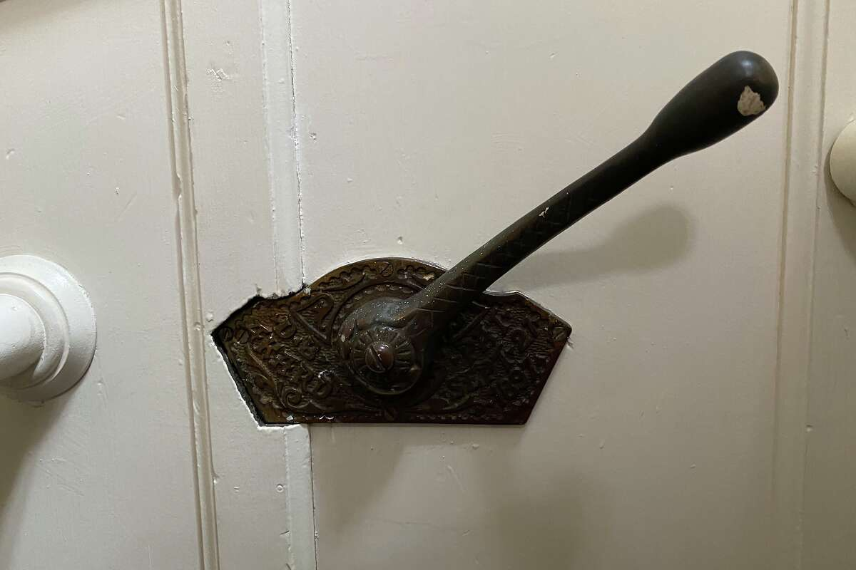 A bell crank lever at the top of the stairs in a North Beach apartment.