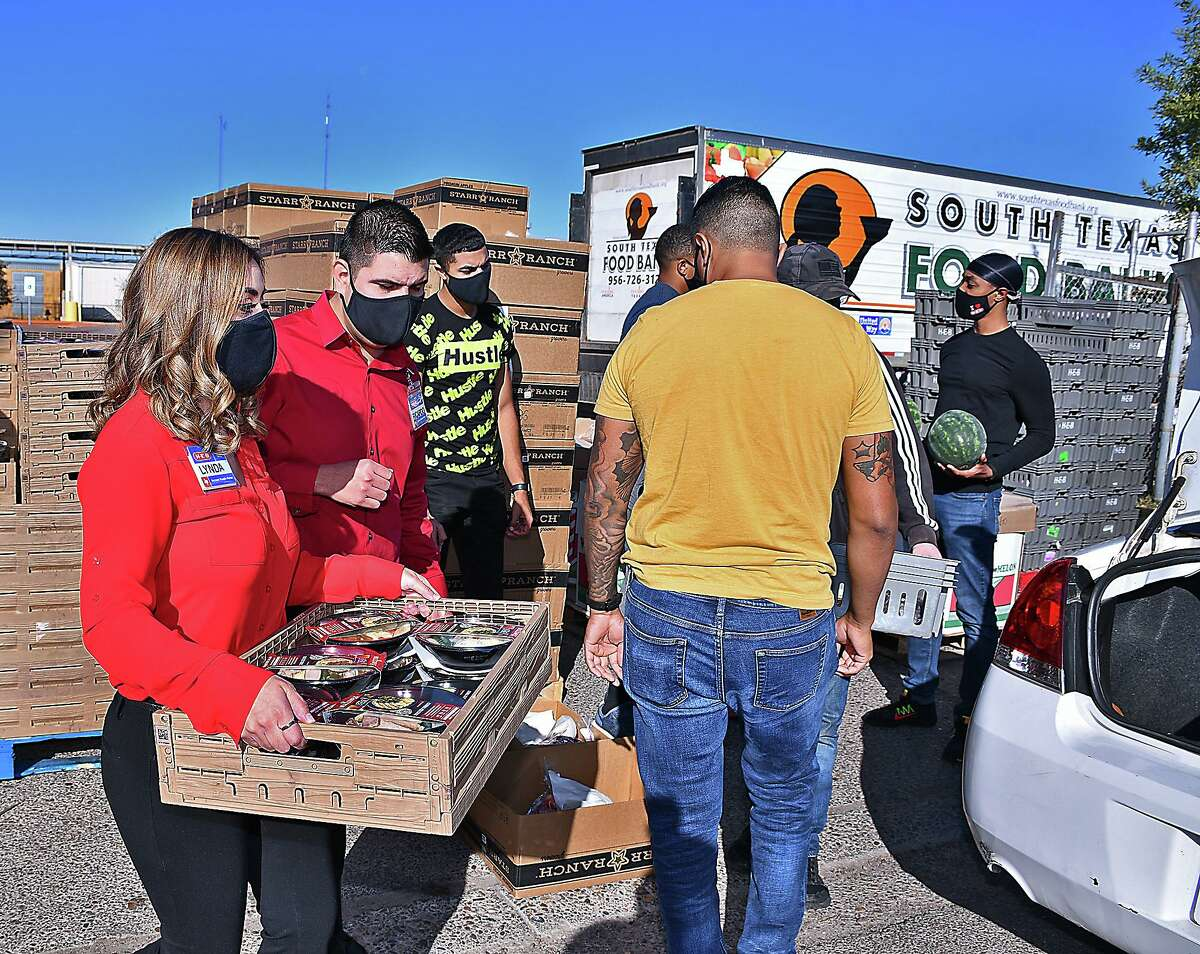 H-E-B representatives Lynda Villarreal and Ricardo Garcia hand out some of the Thanksgiving dinners that were distributed at the South Texas Food Bank Wednesday, November 4, 2020. The distribution was part of the annual Feast of Sharing event. The H-E-B Meal Simple holiday dinners consisted of roasted turkey, green beans and mashed potatoes with garlic butter.