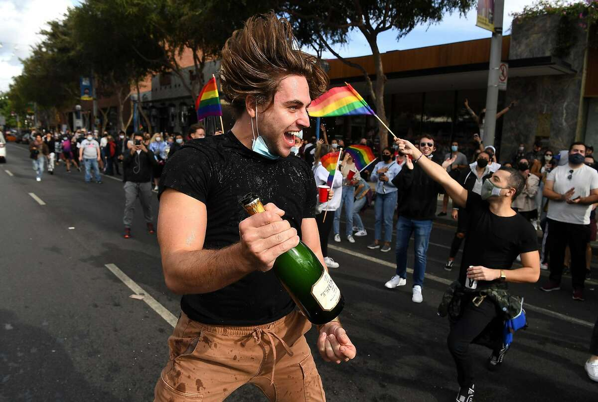 People celebrate in West Hollywood on Saturday following the declaration of victory for President-elect Joe Biden and Vice-president-elect Kamala Harris. Health experts are concerned that revelers could let their guard down and allow the coronavirus to spread amid a national surge.