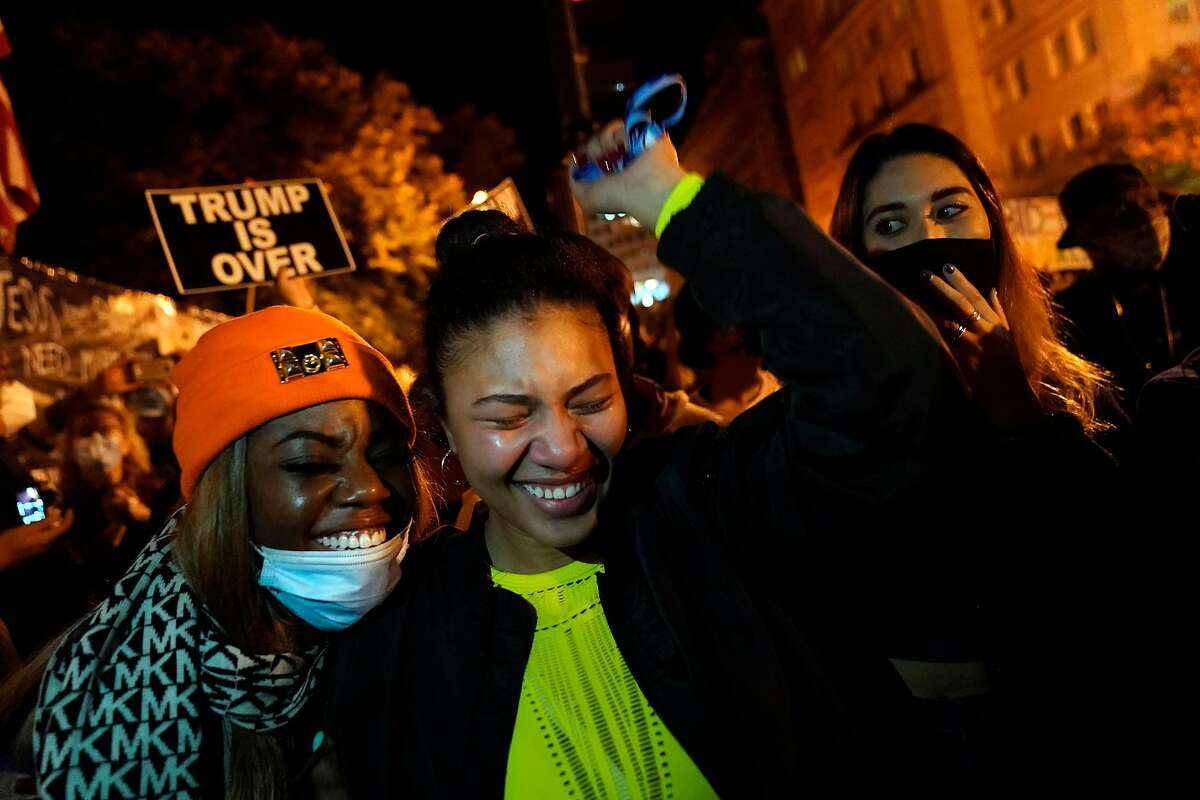 Women cheer during a watch party near the White House as they listen to President-elect Joe Biden deliver his victory speech on Saturday. Coronavirus can spread through crowds, health experts warn.