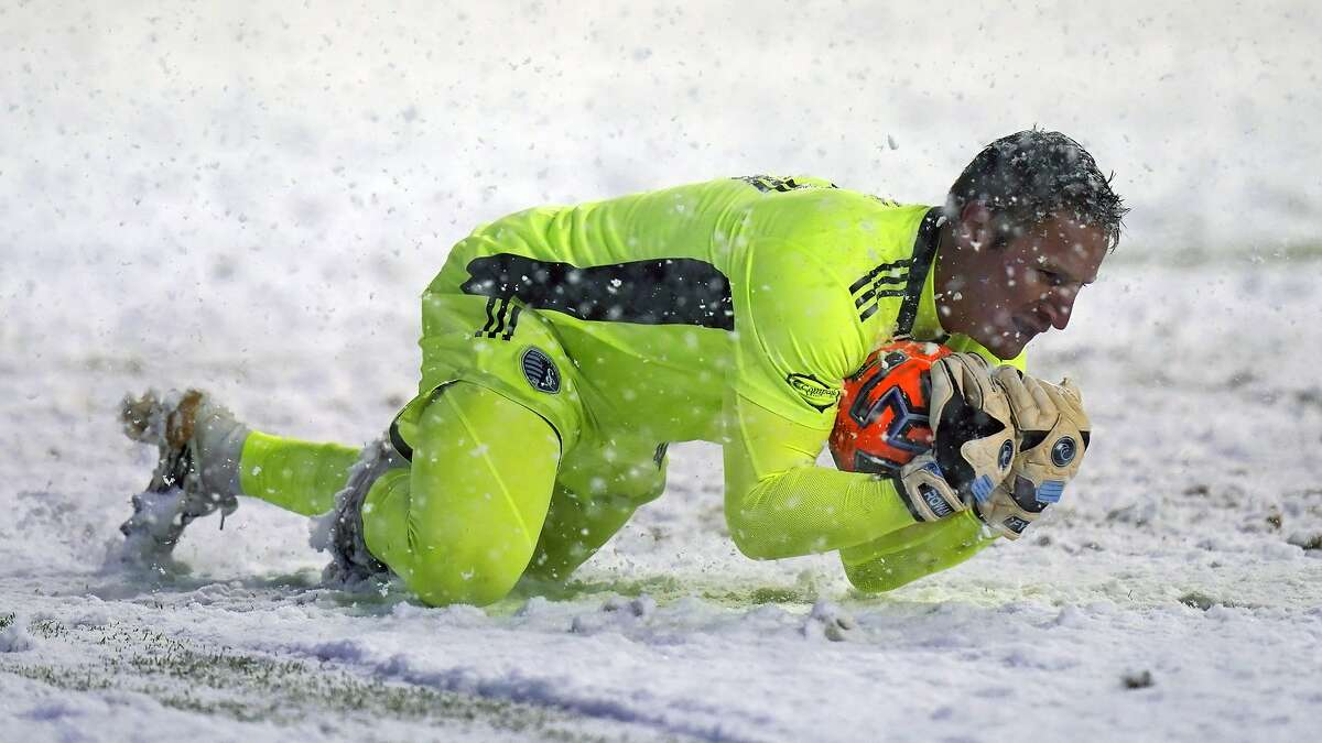 Sporting Kansas City goalkeeper Tim Melia makes a save in the snow against host Real Salt Lake.
