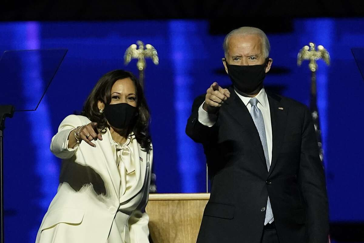 Vice President-elect Kamala Harris and President-elect Joe Biden wave on stage together, Saturday, Nov. 7, 2020, in Wilmington, Del.