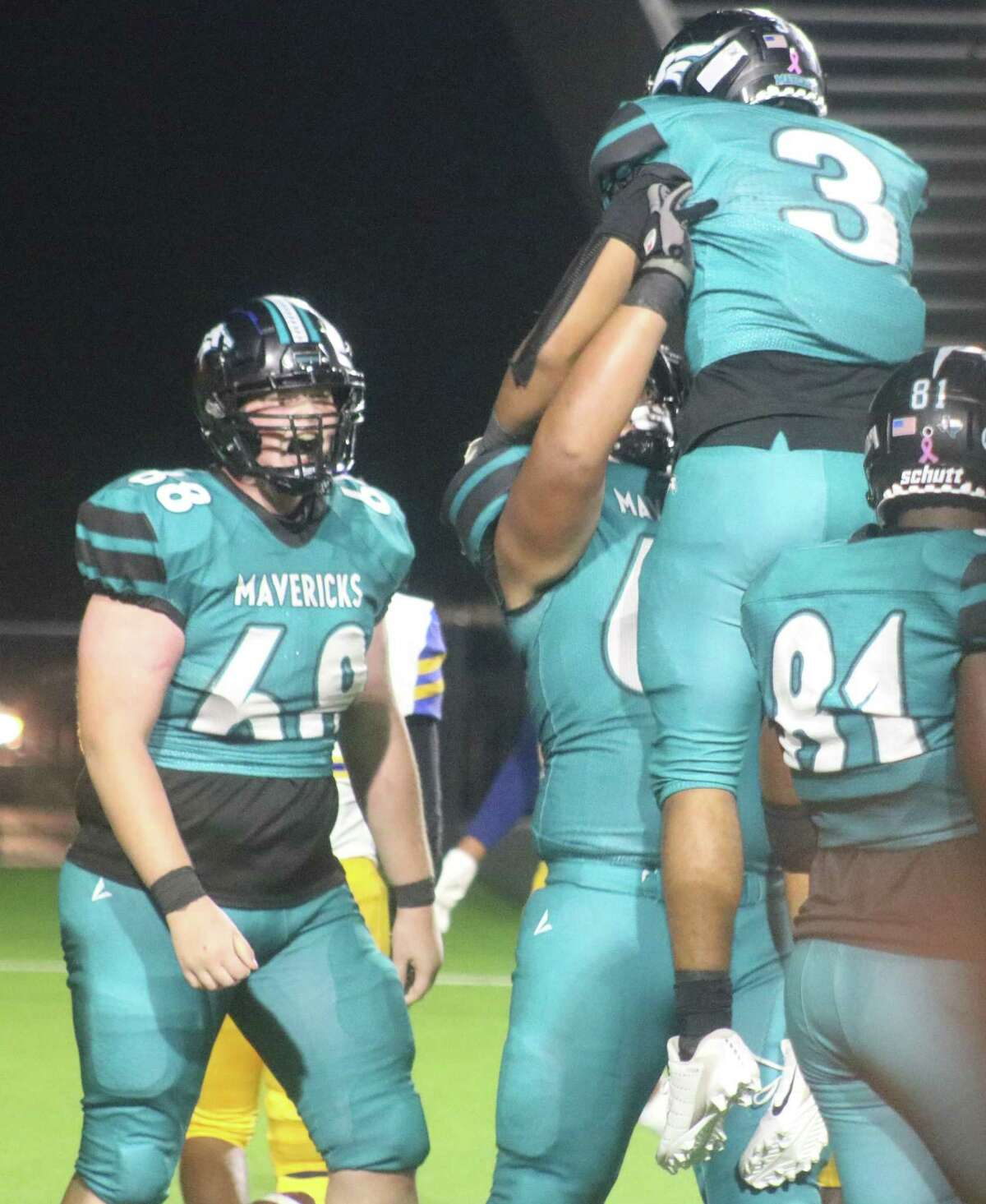 Memorial's Christian Vega leaps into the arms of a teammate after scoring the last of the team's come-from-behind fourth quarter touchdowns. Looking on is lineman Jerry Barr (68).