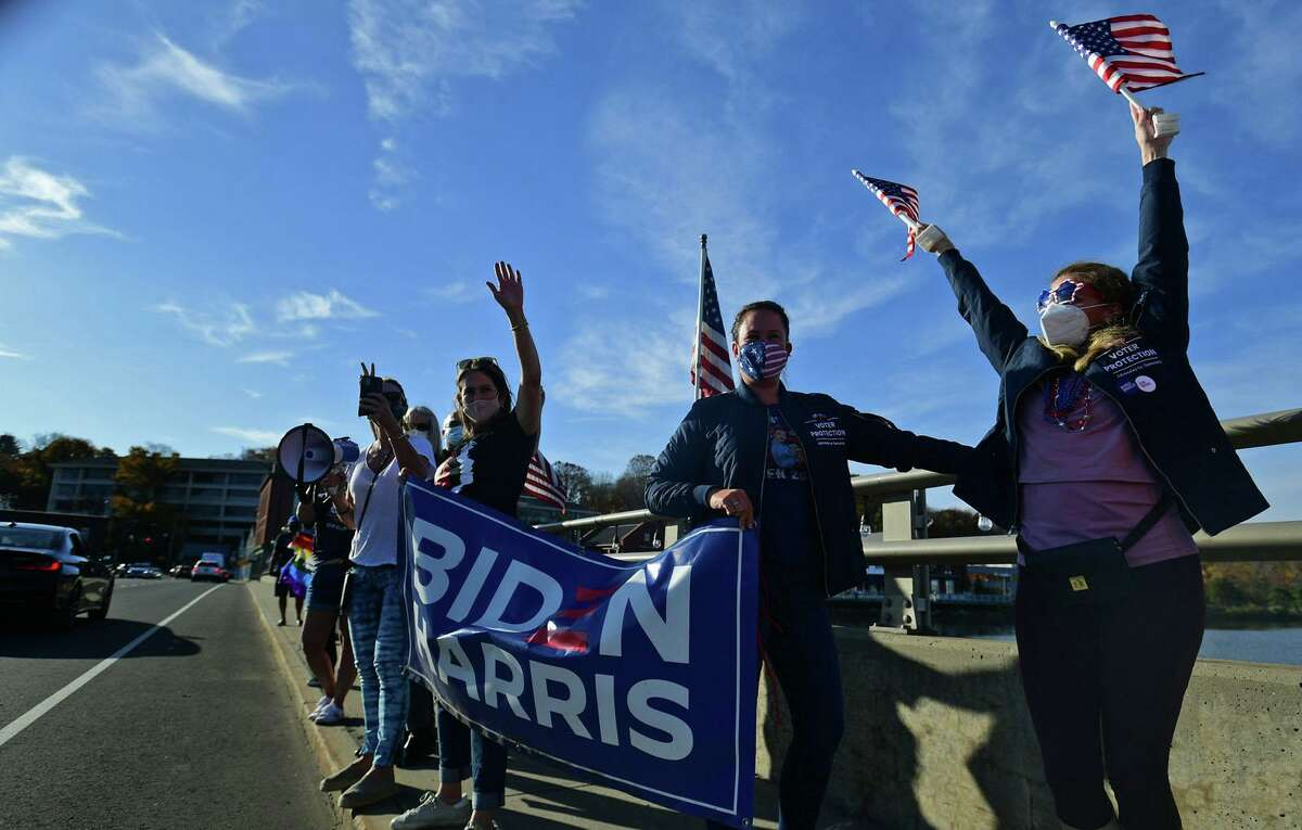 Local residents gather at the Ruth Steinkraus bridge in downtown Westport to celebrate the Biden-Harris declaration of victory in the US presidential election Saturday, November 7, 2020, in Westport, Conn.