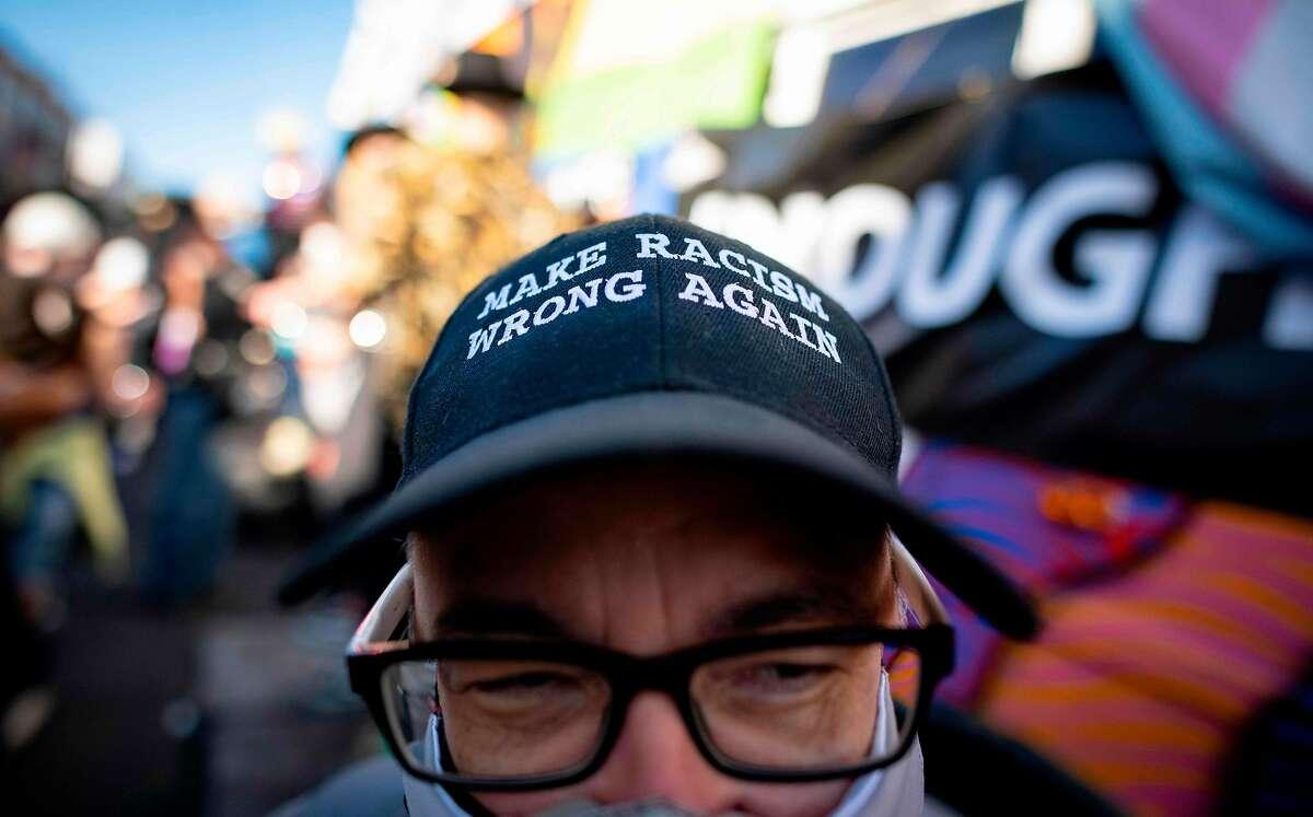 A man wearing an anti-racism hat celebrates Joe Biden's election in the Castro neighborhood of San Francisco on Saturday.