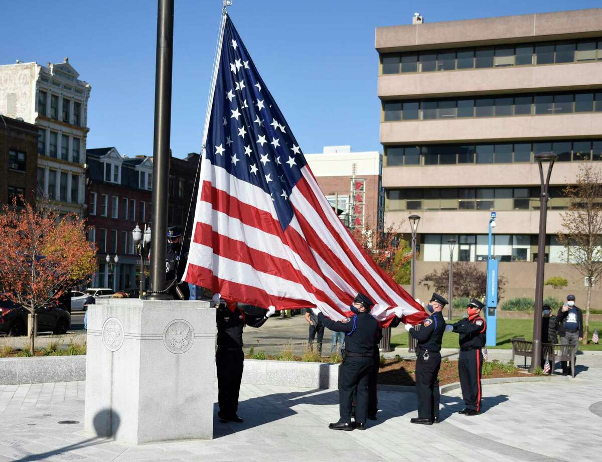 The Stamford Police Department honor guard raise the flag during the Veterans Day ceremony on Sunday