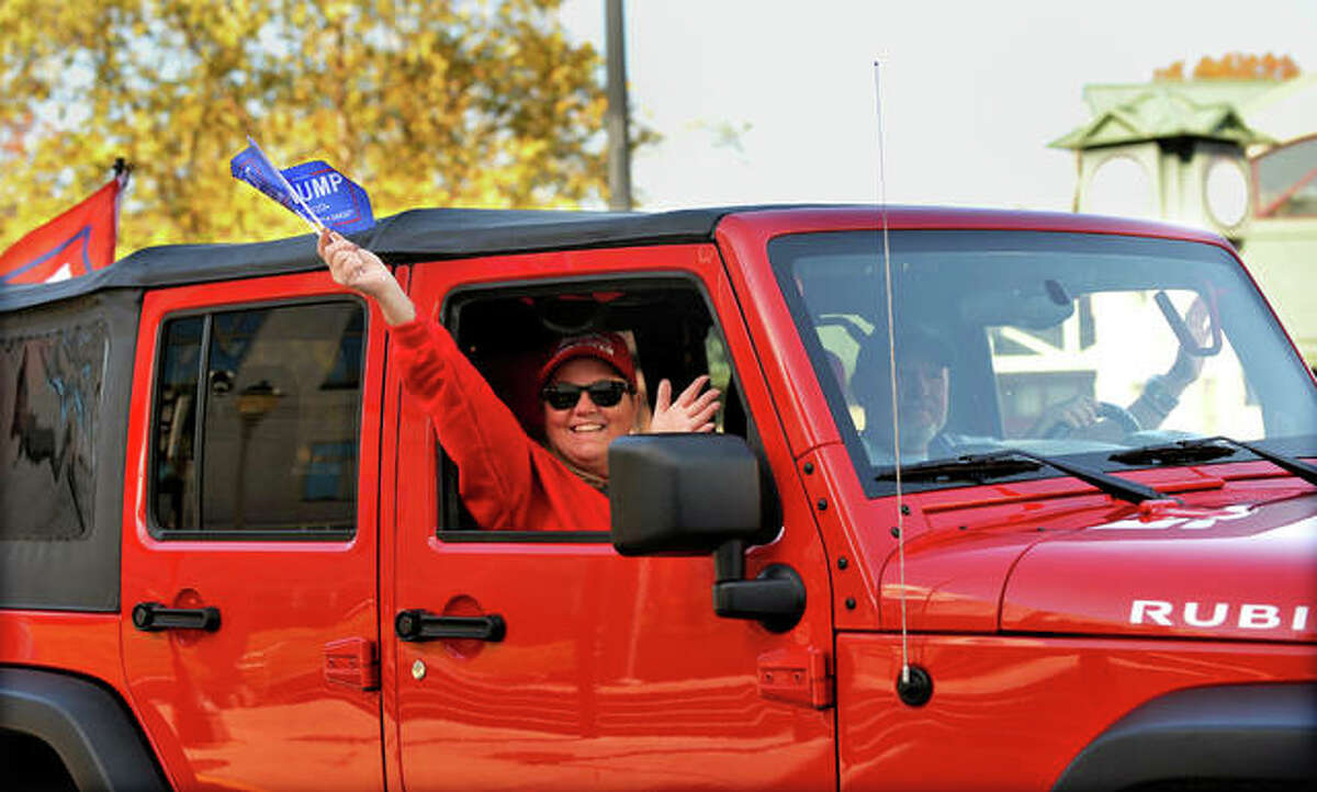 A couple of Trump supporters wave as they drive by as part of a large number of vehicles that drove down North Main Street in Edwardsville on Nov. 1. Many of the vehicles were decorated with Trump flags as well as American flags and anti-Biden signs.
