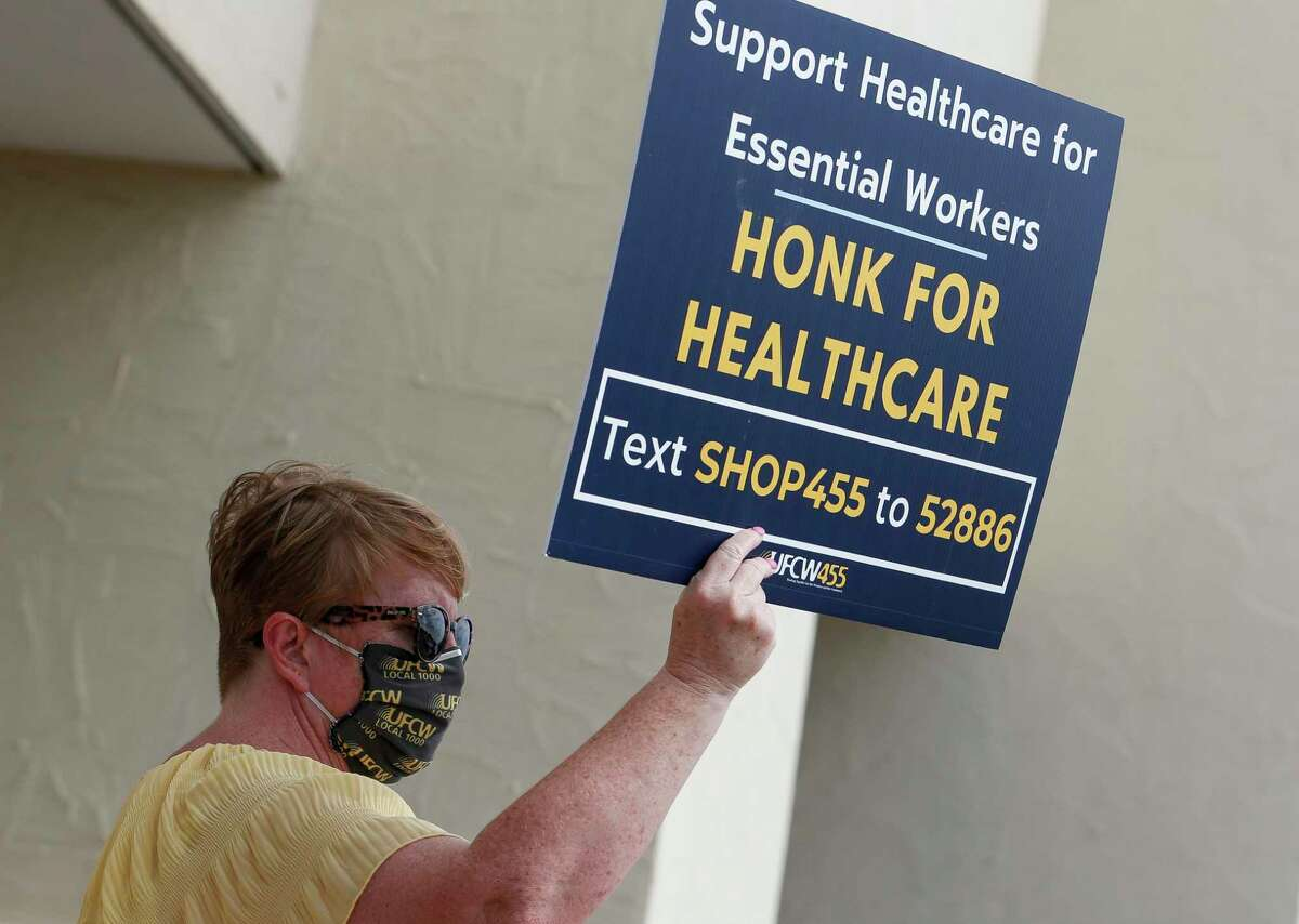 Debra Donwerth, with United Food and Commercial Workers International Union Local 455, holds up sign outside a Kroger store during a rally Tuesday, Sept. 15, 2020, in Houston. Workers represented by UFCW's Local 455, which covers Louisiana and a large swath of Texas, began voting last week on whether to authorize a strike.