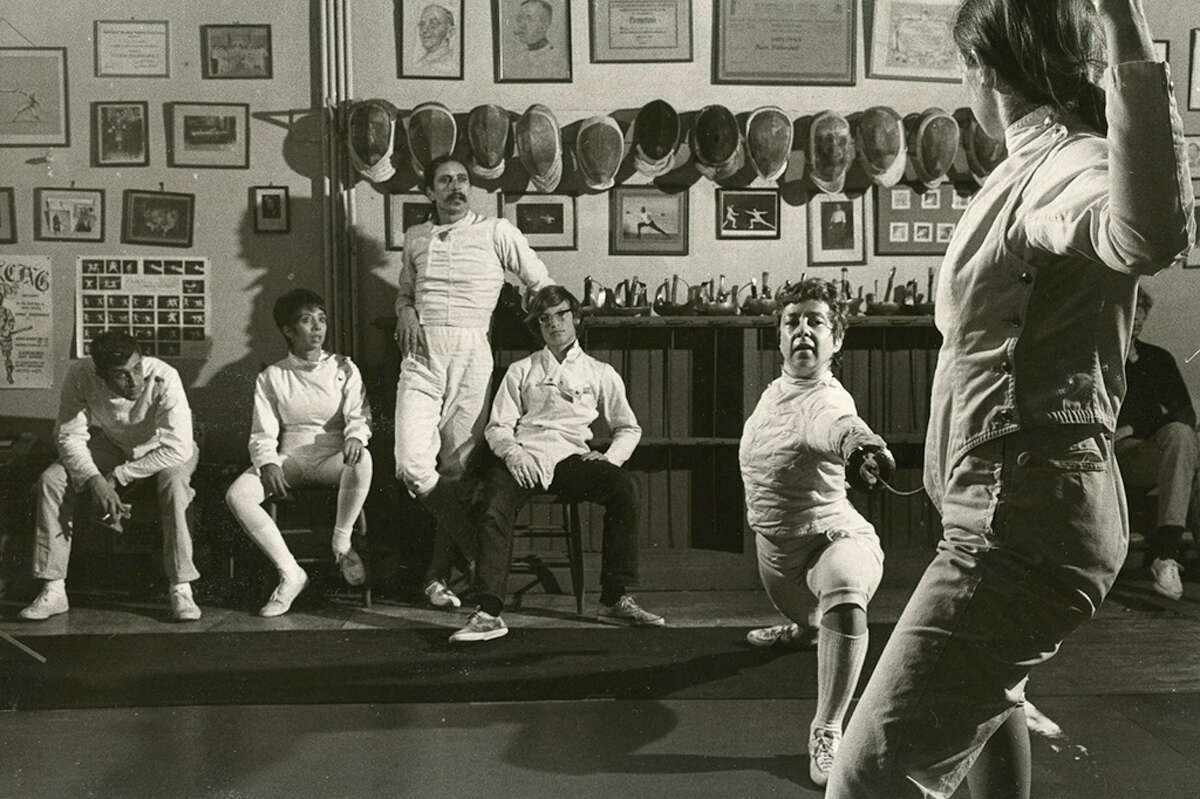 Michael D'Asaro standing in the center in the back at the Halberstadt fencing club. Three-time national foil champion Harriet King is demonstrating the lunge. She won two championships under D'Asaro's coaching.