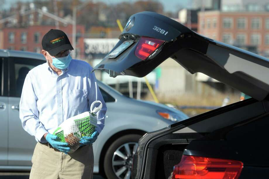Volunteer Rick Amill, of Norwalk, places a frozen turkey in the trunk of a waiting car during Connecticut Food Bank's drive-through turkey distribution in Veteran's Memorial Park, in Norwalk, Conn. Nov. 9, 2020. Photo: Ned Gerard / Hearst Connecticut Media / Connecticut Post