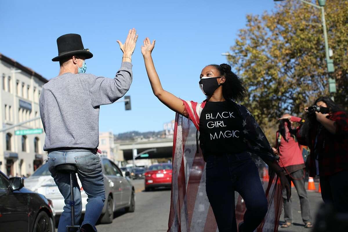 Wearing a Black Girl Magic T-shirt, Lia Ballard of Oakland celebrates on Grand Avenue after Joe Biden captured the presidential victory over Donald Trump on Saturday.