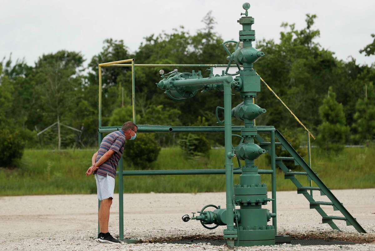 Jim Estes takes a close look at the wellhead of an oil well located on the lot that's behind his home Monday, June 29, 2020, in League City, Texas.