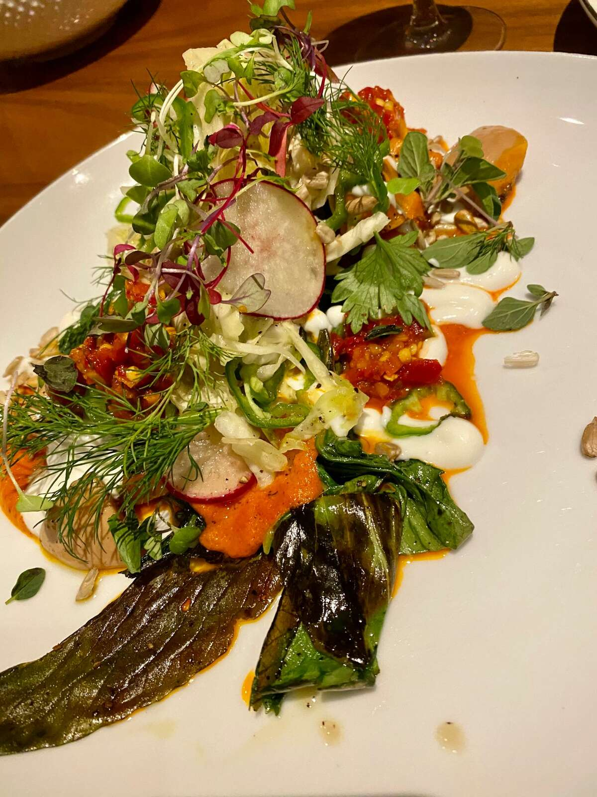 Fire-grilled bok choy with piquillo purée, sweet-pepper relish, slivered radishes and jalapenos at Local 111 in Philmont. (Susie Davidson Powell for the Times Union.)