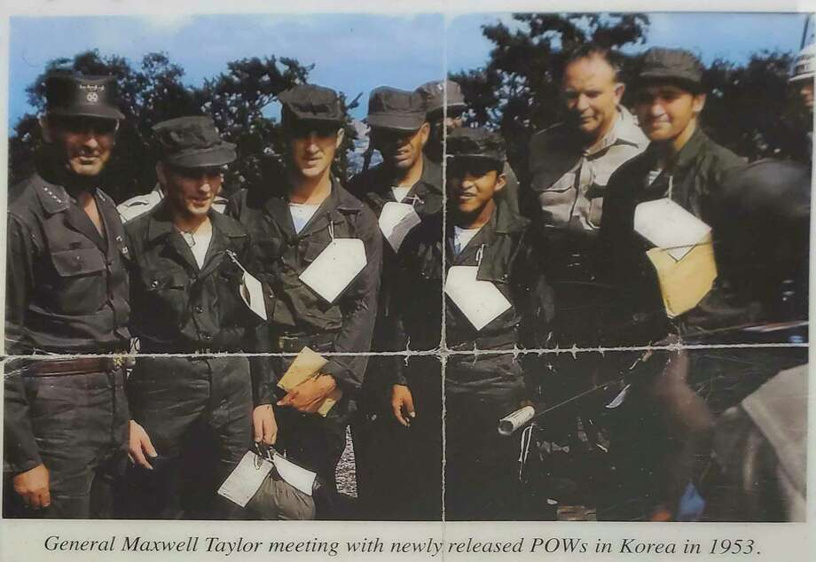 Years after being released from captivity, Deming stumbled across this photo of he (second from the left) and many several others meeting General Maxwell Taylor after they were released. Deming has carried the photo folded in his wallet since finding it.