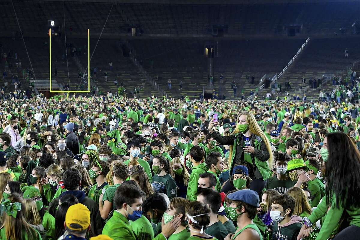 Fans storm the field after Notre Dame defeated the Clemson 47-40 in two overtimes in an NCAA college football game Saturday, Nov. 7, 2020, in South Bend, Ind. (Matt Cashore/Pool Photo via AP)