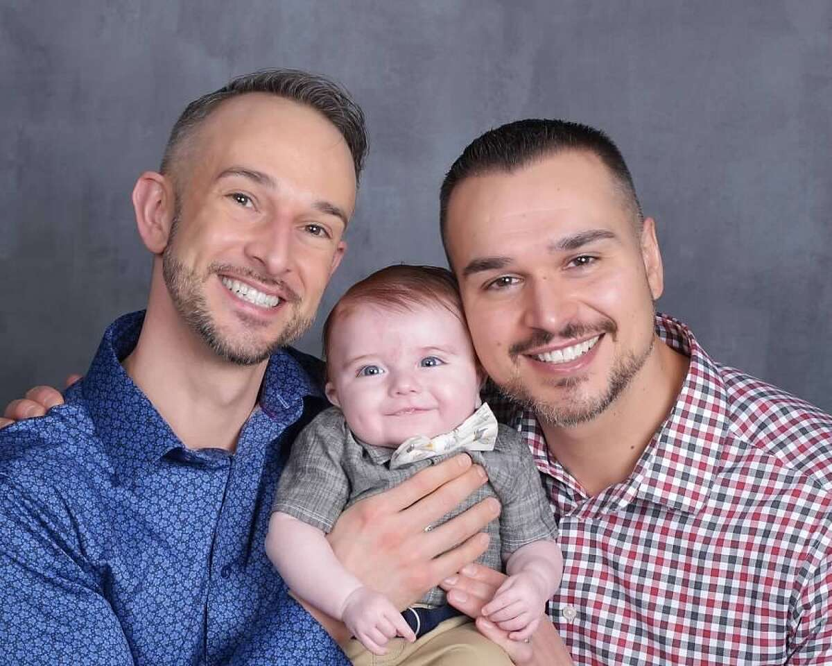 Eric MacDowell, left, and Eric Wilke with their son, Xander, who they adopted through Friends in Adoption.