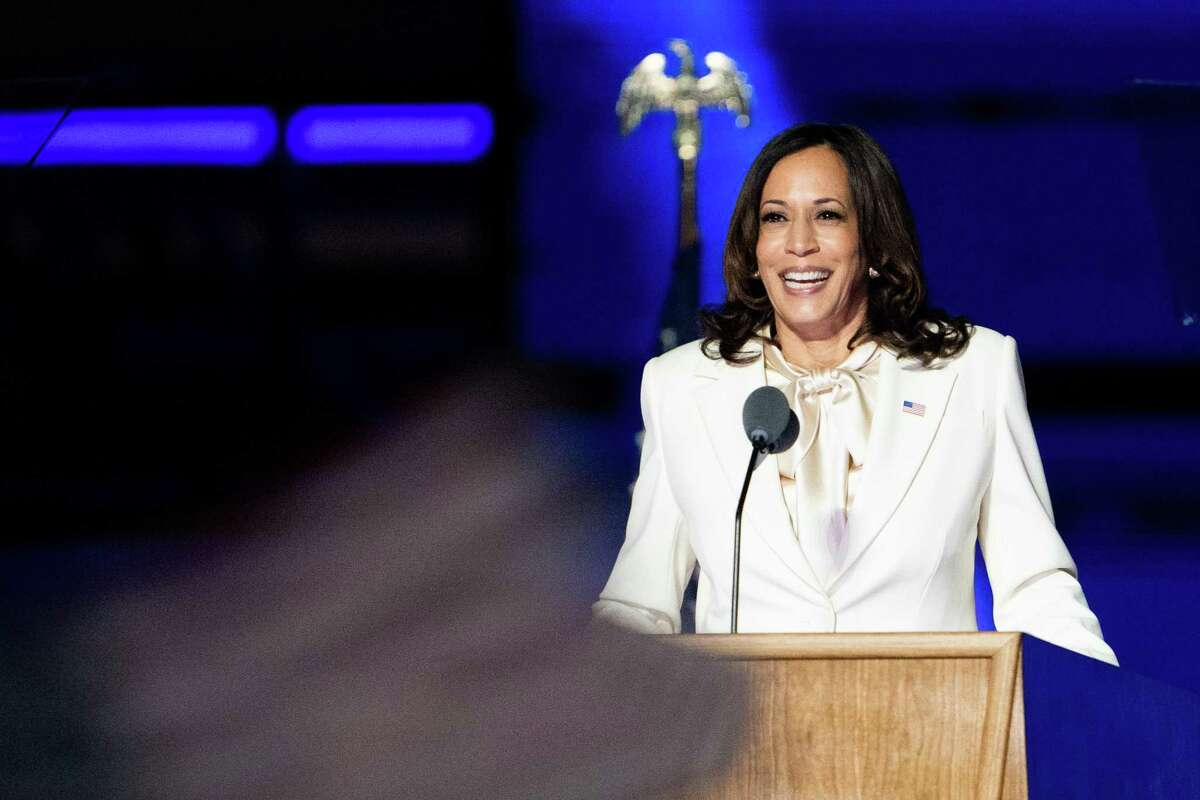 Vice President-elect Kamala Harris delivers remarks in a white suit and a pussy bow.