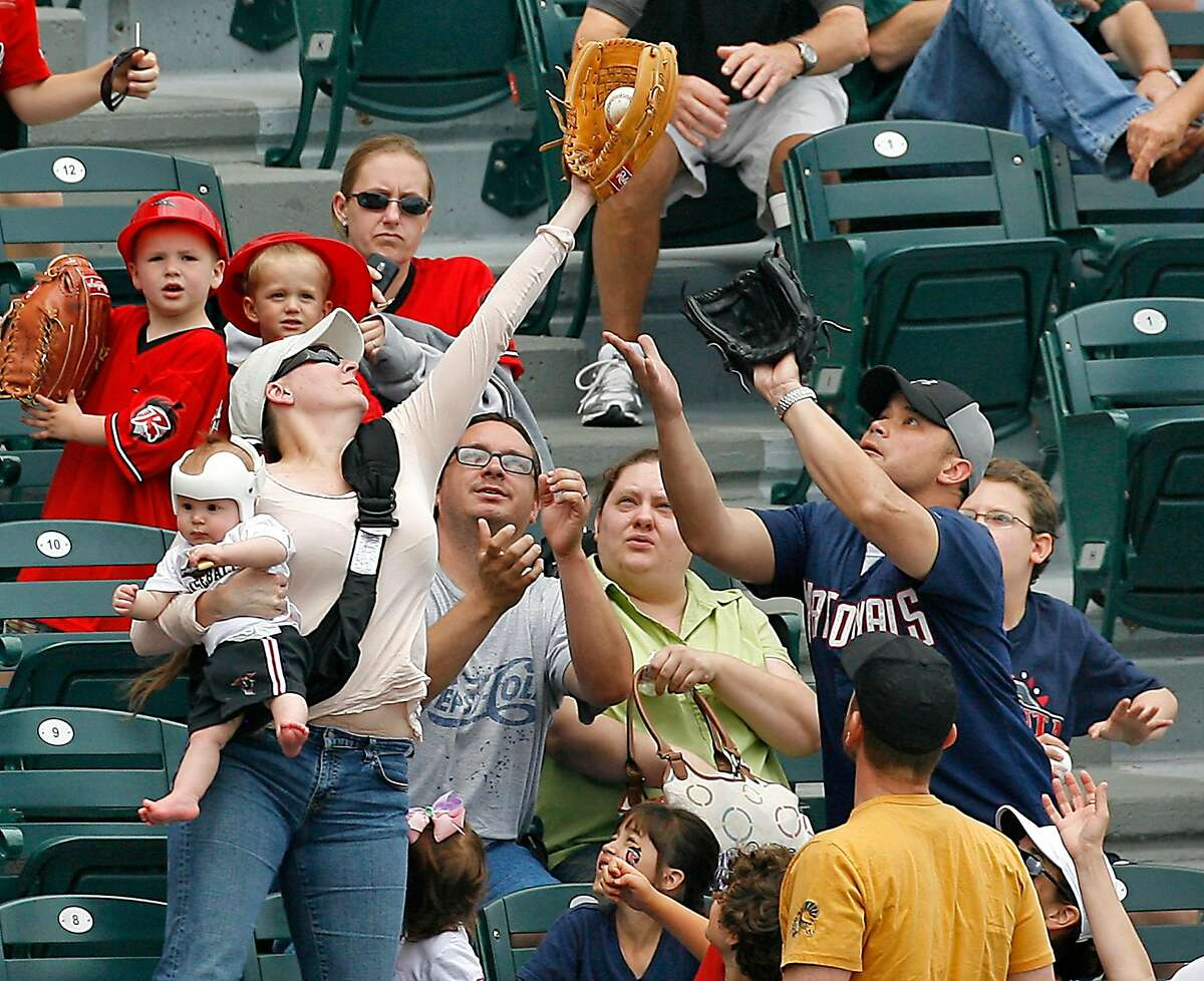 A woman holding her baby catches a foul ball at a 2011 Flying Squirrels game in Richmond, Va. The Squirrels have been the Giants' Double-A affiliate since 2010, but that could change after a realignment in the minors for 2021.