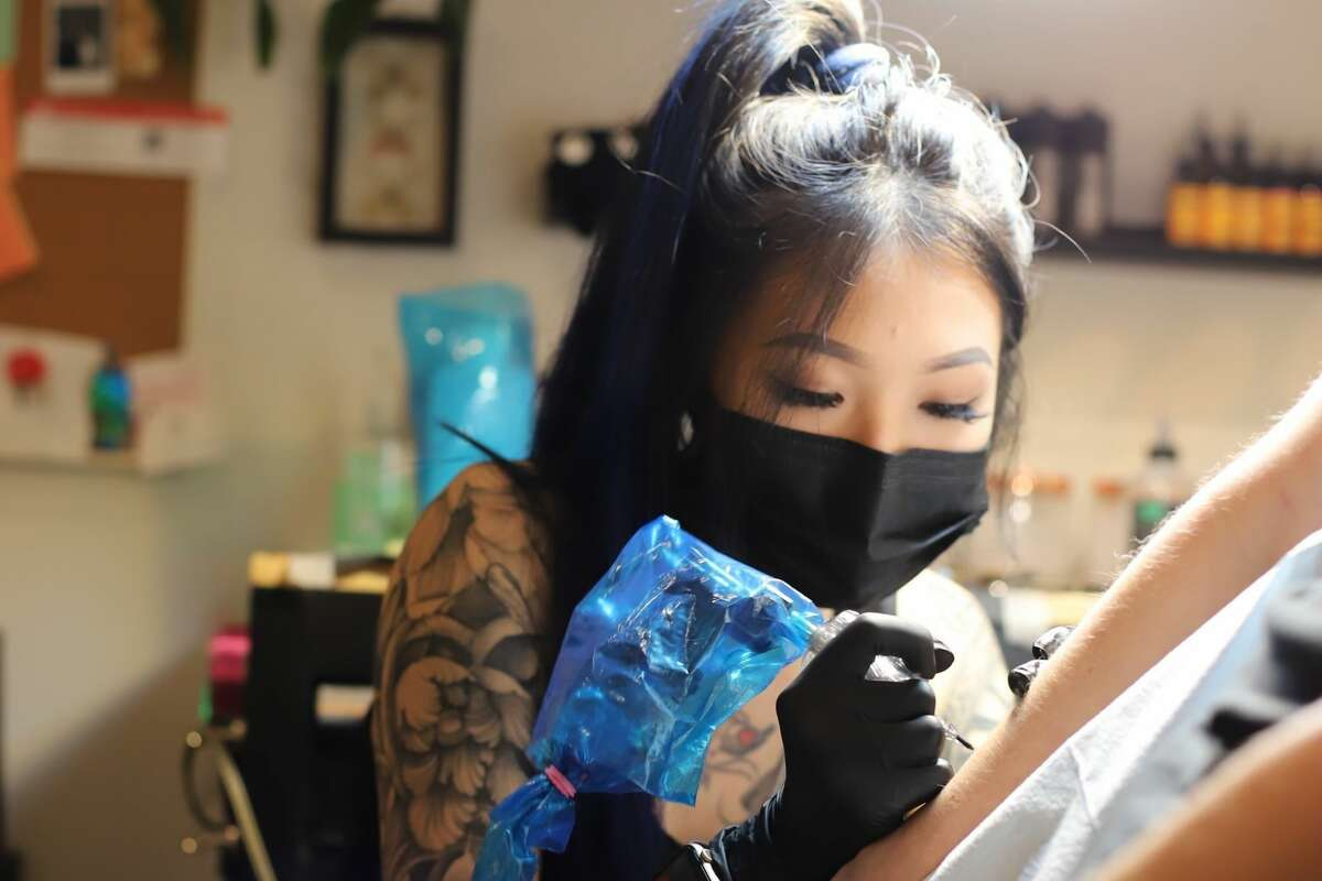 Millie Koh, owner of UNDRGRND, tattoos a client at her shop in San Francisco.