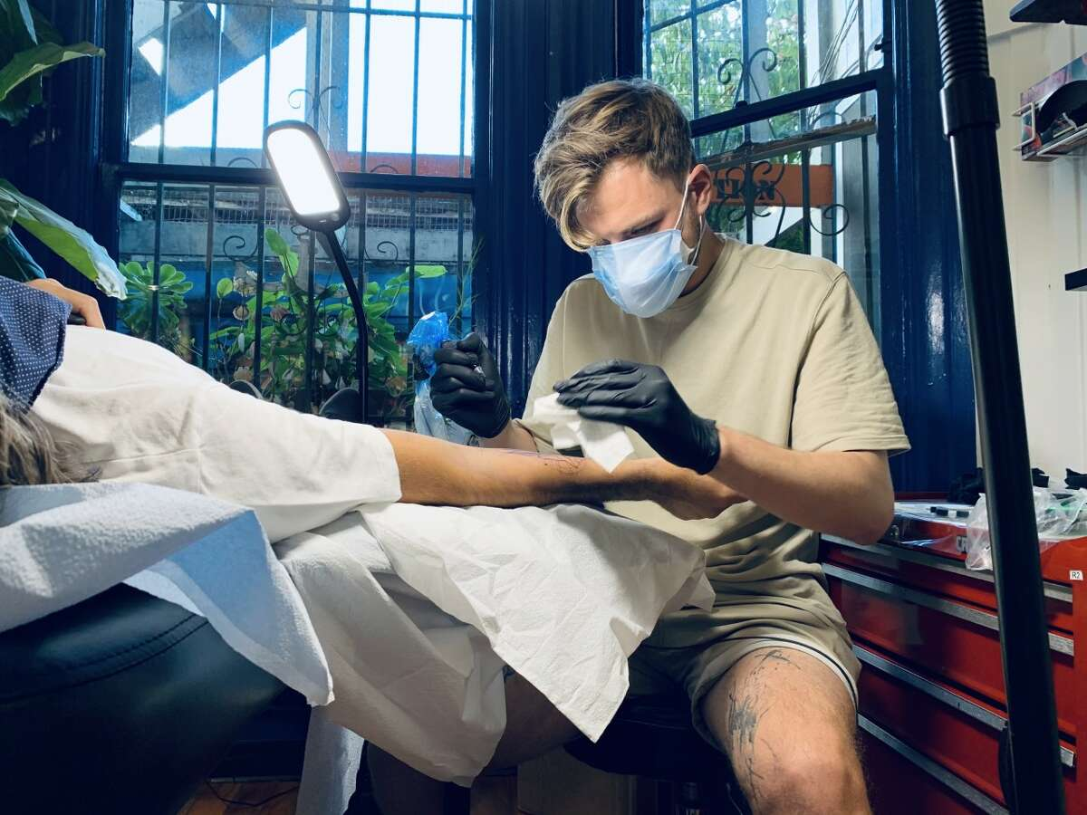 Filip Fabian, an artist at Black + Blue Tattoo, wears two masks as he tattoos one of his recent clients.